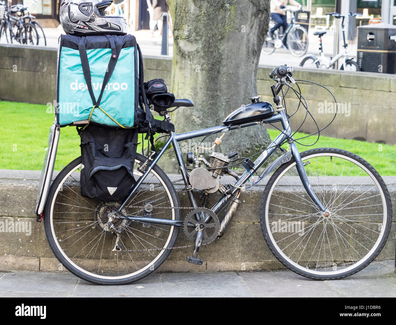A Deliveroo delivery rider's bike, modified with the attachment of a small petrol engine. - Stock Image