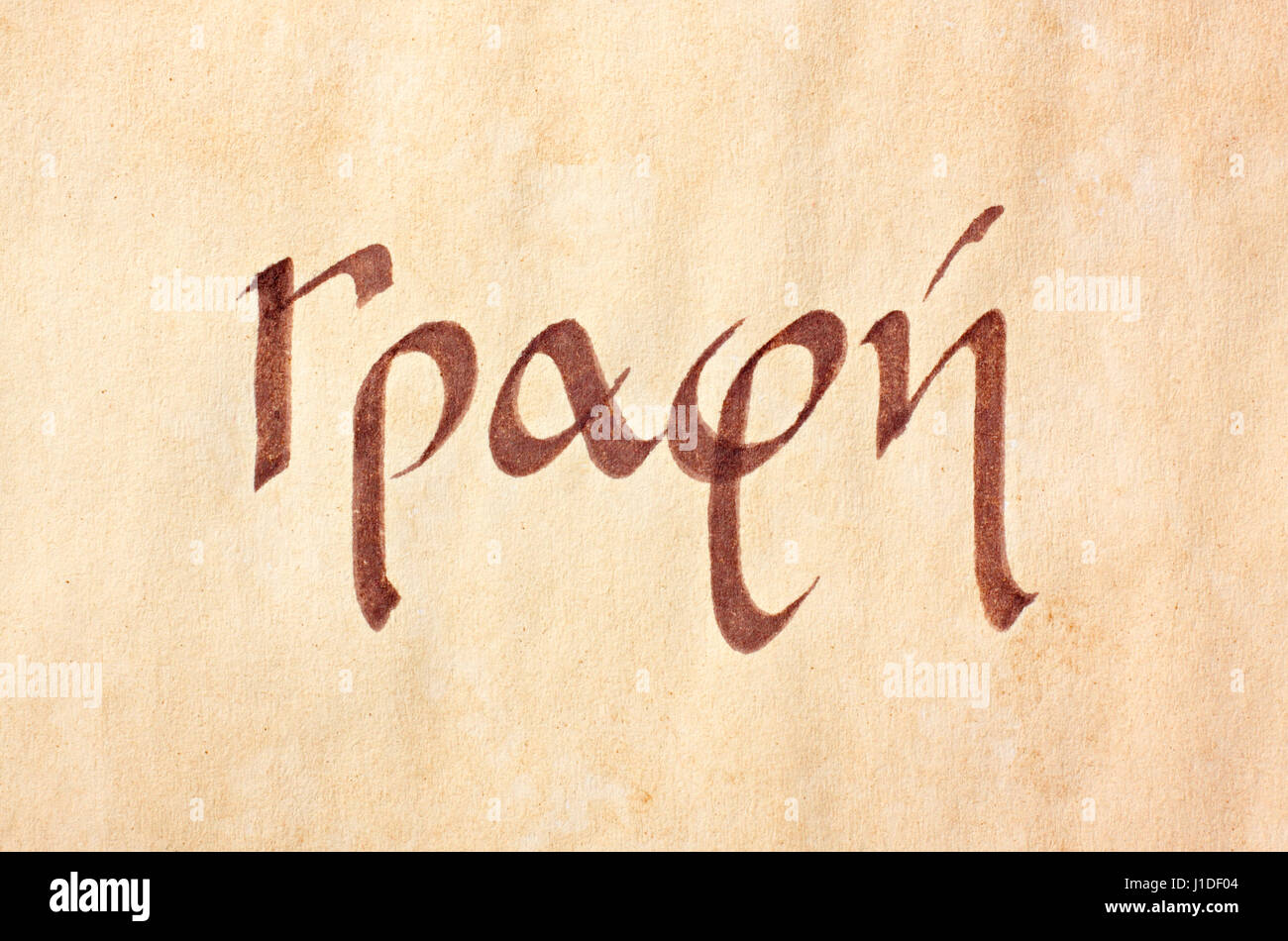 Handwritten word writing in greek language and script on the aged paper - Stock Image