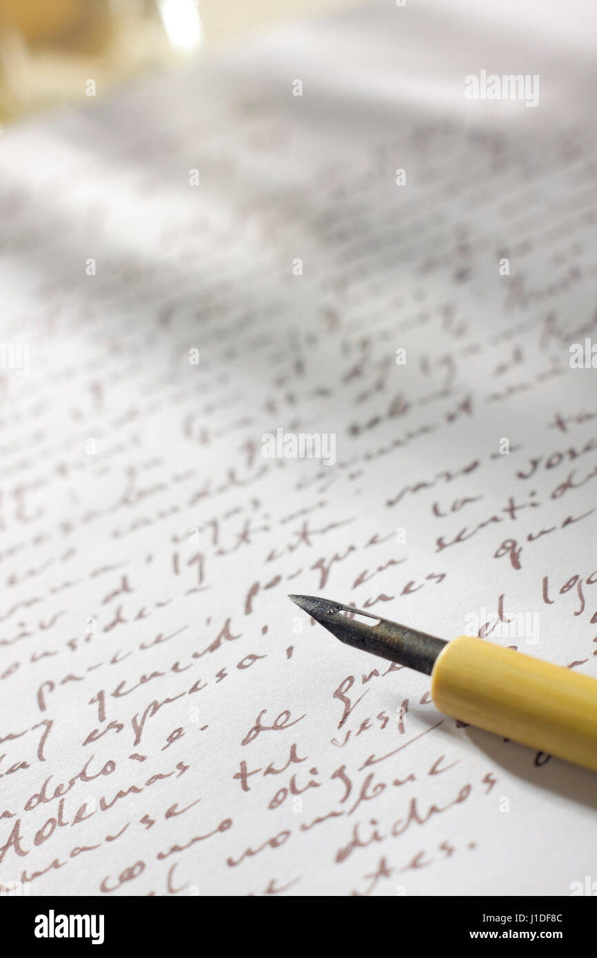 Handwritten correspondence on paper with brown ink, ancient nib pen on first plane and shadows on background - Stock Image