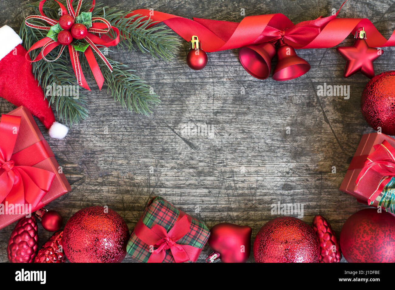 christmas background frame decorations gift boxes with claus hat and red ribbon bow with ornament bauble on vintage wooden table with copy space still