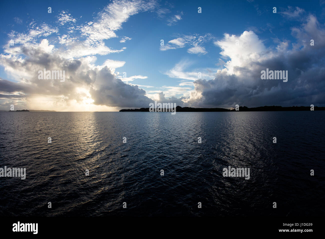 A beautiful sunrise appears over tropical lagoon waters in the Republic of Palau. This Micronesian country is a - Stock Image