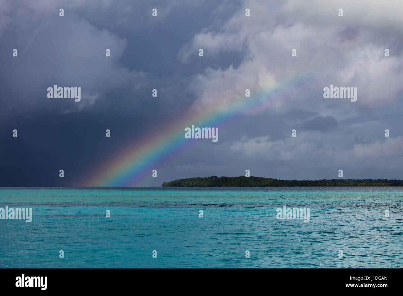 A Beautiful Rainbow Appears Over Tropical Lagoon Waters In The Stock Photo Alamy
