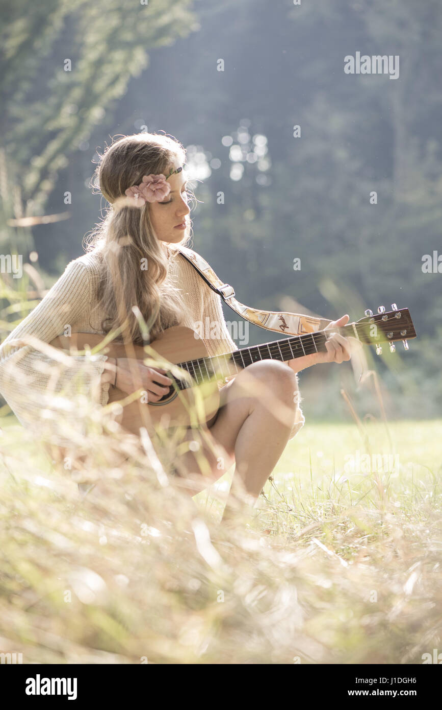 Young singer song-writer musician guitar girl in autumn forest, Vienna, Austria (model-released) - Stock Image