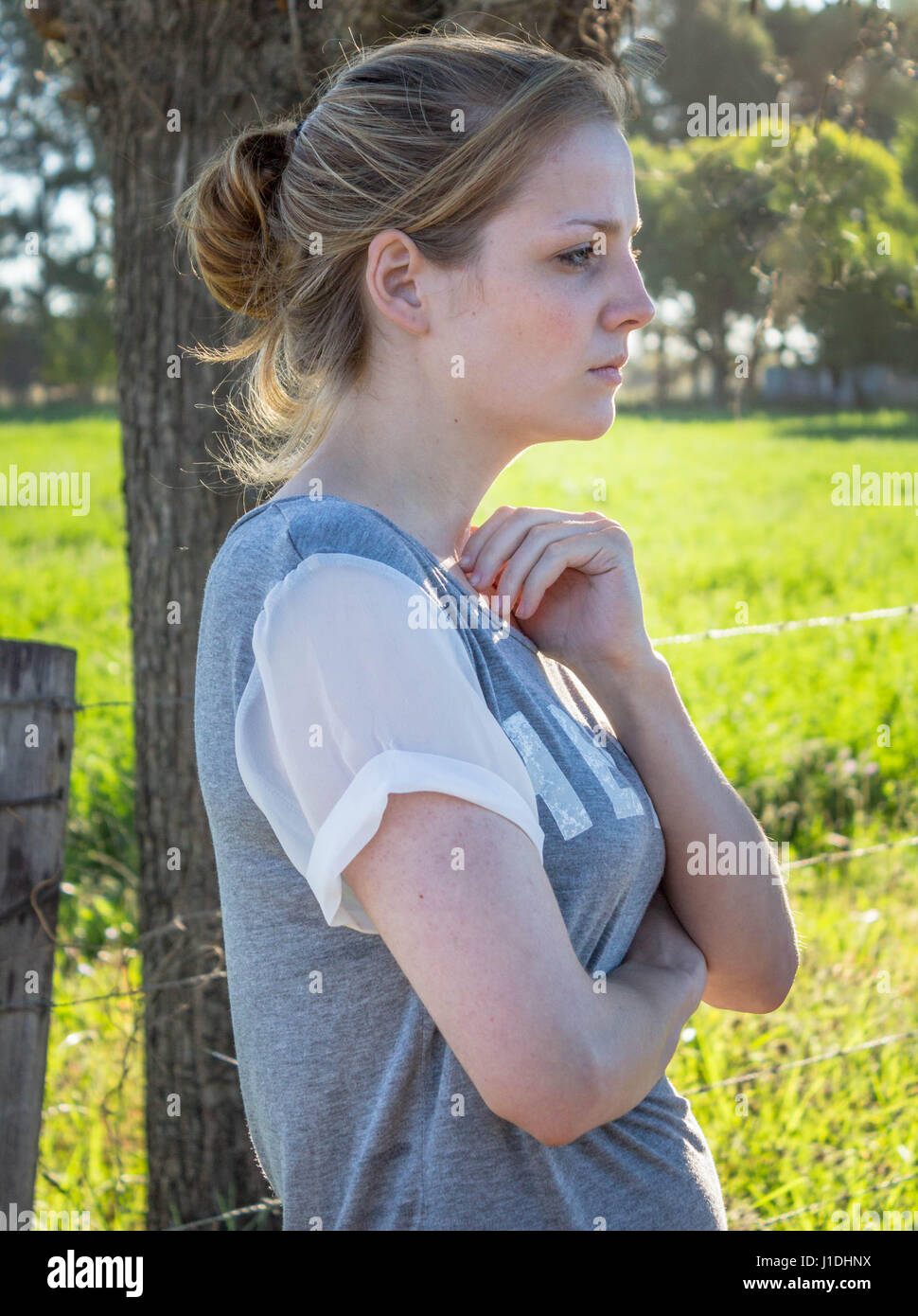 Portrait of serious young blonde woman looking ahead and away from camera standing in the shade under a tree in - Stock Image