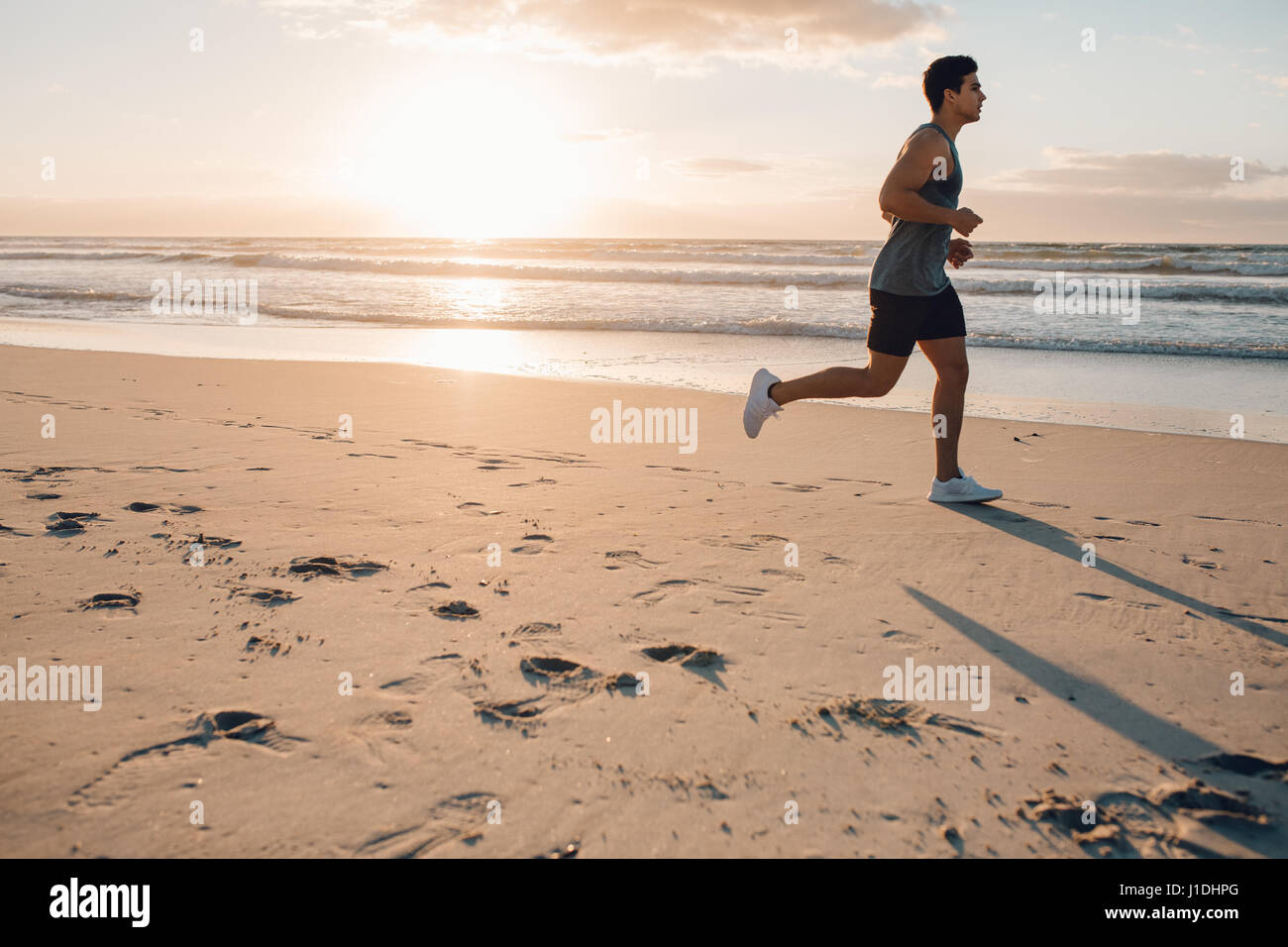 Side view shot of fit young man running on the beach in morning. Healthy male model jogging on the sea shore. - Stock Image