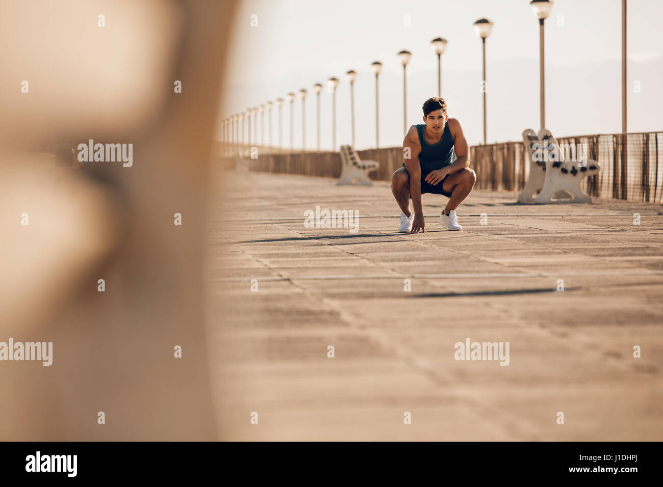 Shot of healthy young man taking a break after morning run. Male runner resting after running on promenade. - Stock Image