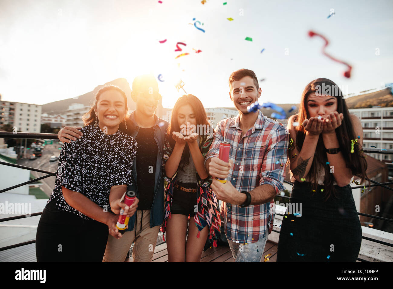 Group of friends hanging out together and blowing confetti on rooftop party. - Stock Image