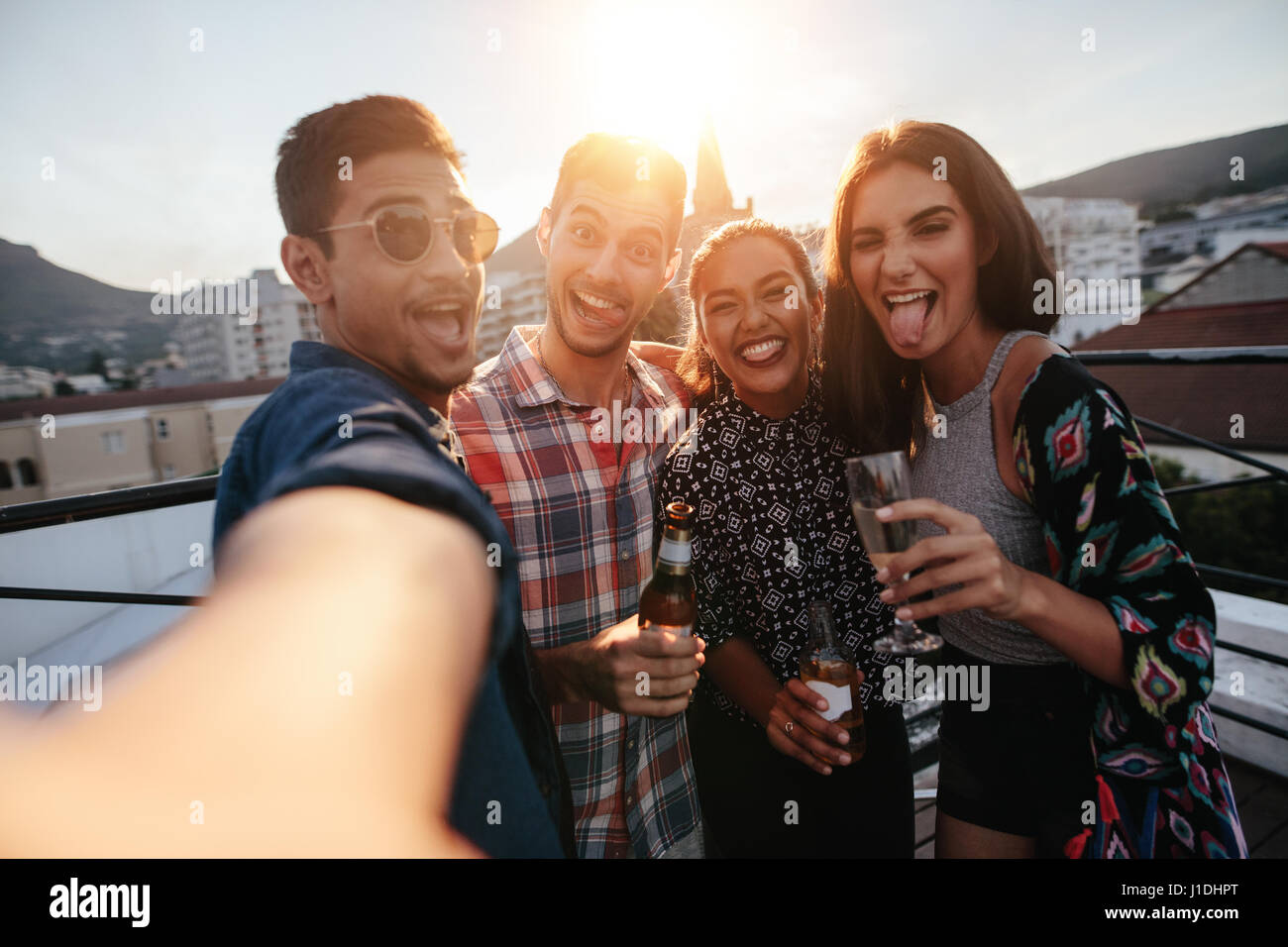 Group of people having a party on the rooftop making a selfie. Happy young friends taking self portrait during party. Stock Photo