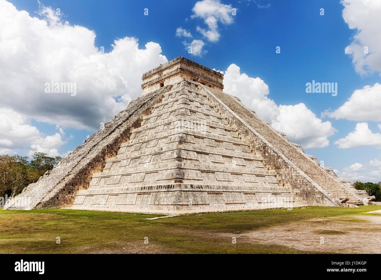 In the ancient Mayan site known as  Chechen Itza, under a bright blue sky with large scattered clouds stand El Castillo, - Stock Image