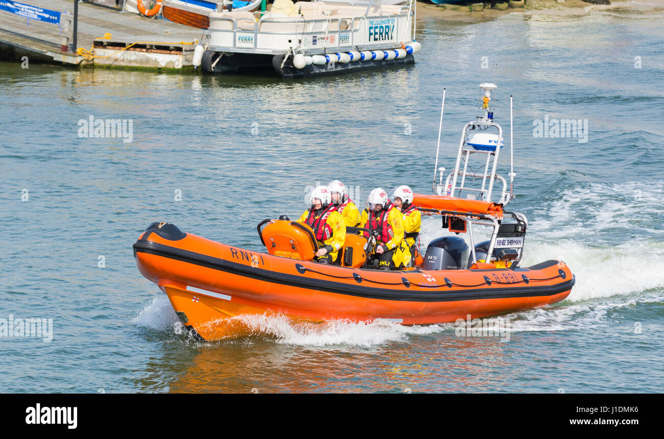 RNLI crew speeding up a river estuary in a lifeboat rib on the River Arun, Littlehampton, West Sussex, England, Stock Photo