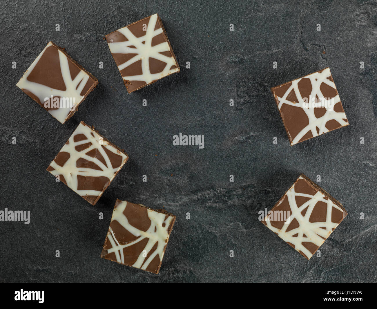 Individual Decorated and Iced Chocolate Tiffin Cakes Against a Black Background - Stock Image
