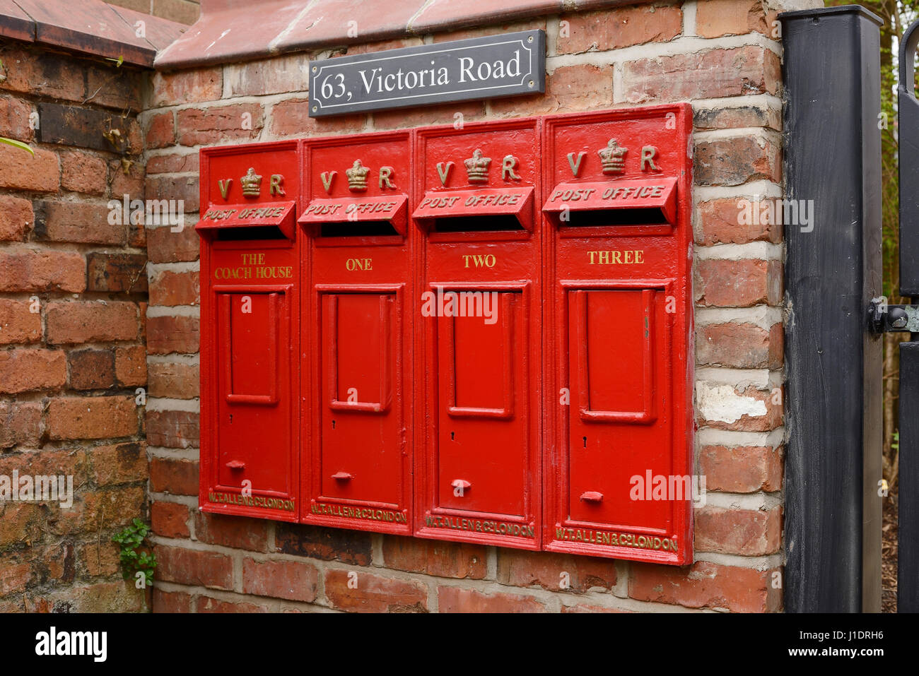 A row of four vintage reproduction mail boxes outside a multi occupancy property. - Stock Image