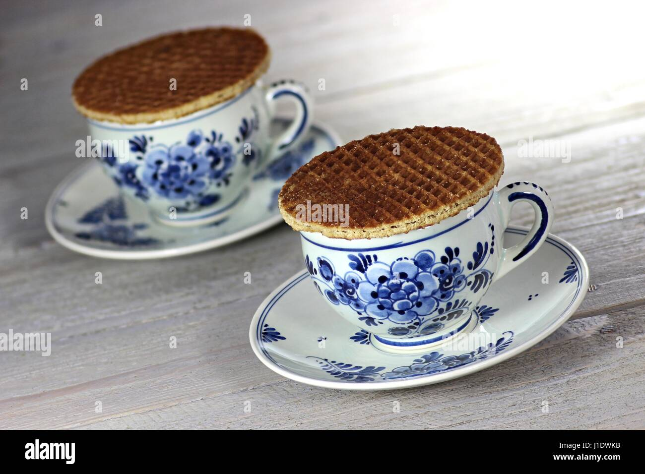 traditional Dutch syrup waffles with Delftware on wooden background - Stock Image