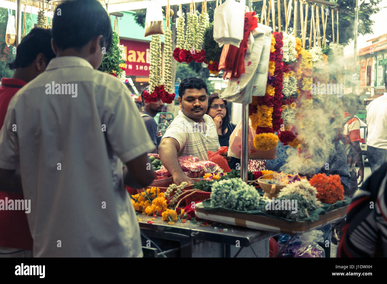 An Indian street vendor selling flowers and garlands in a busy street market in little India, Singapore, southeast - Stock Image