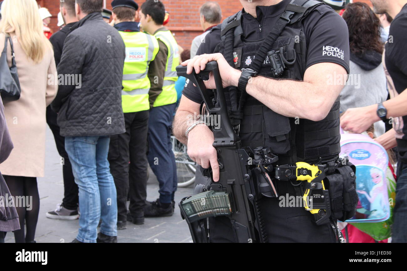 An armed South Wales Police officer oversees the crowd