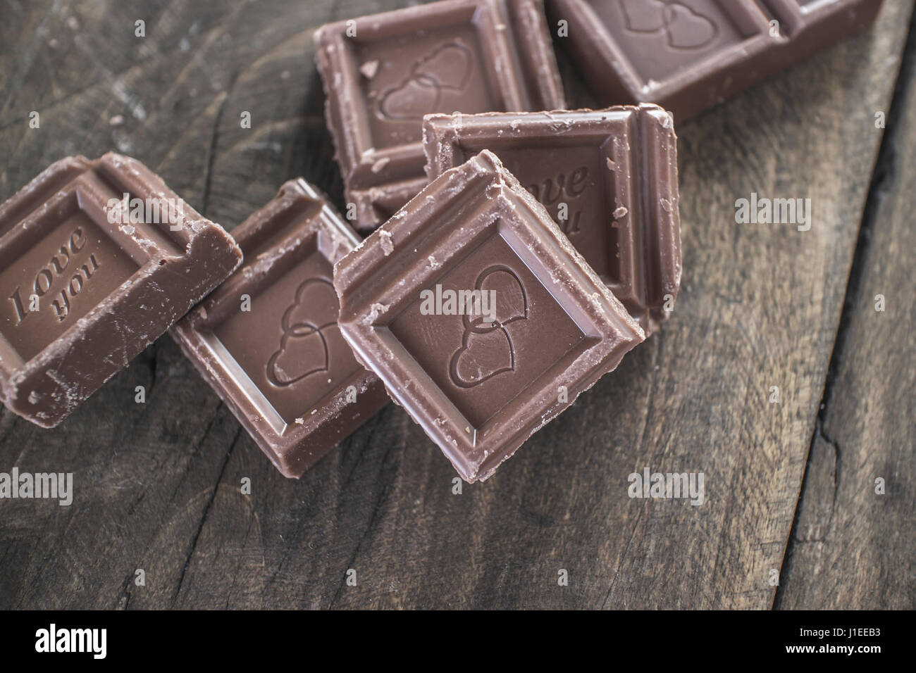 Pieces of  chocolate on wooden background, from above - Stock Image