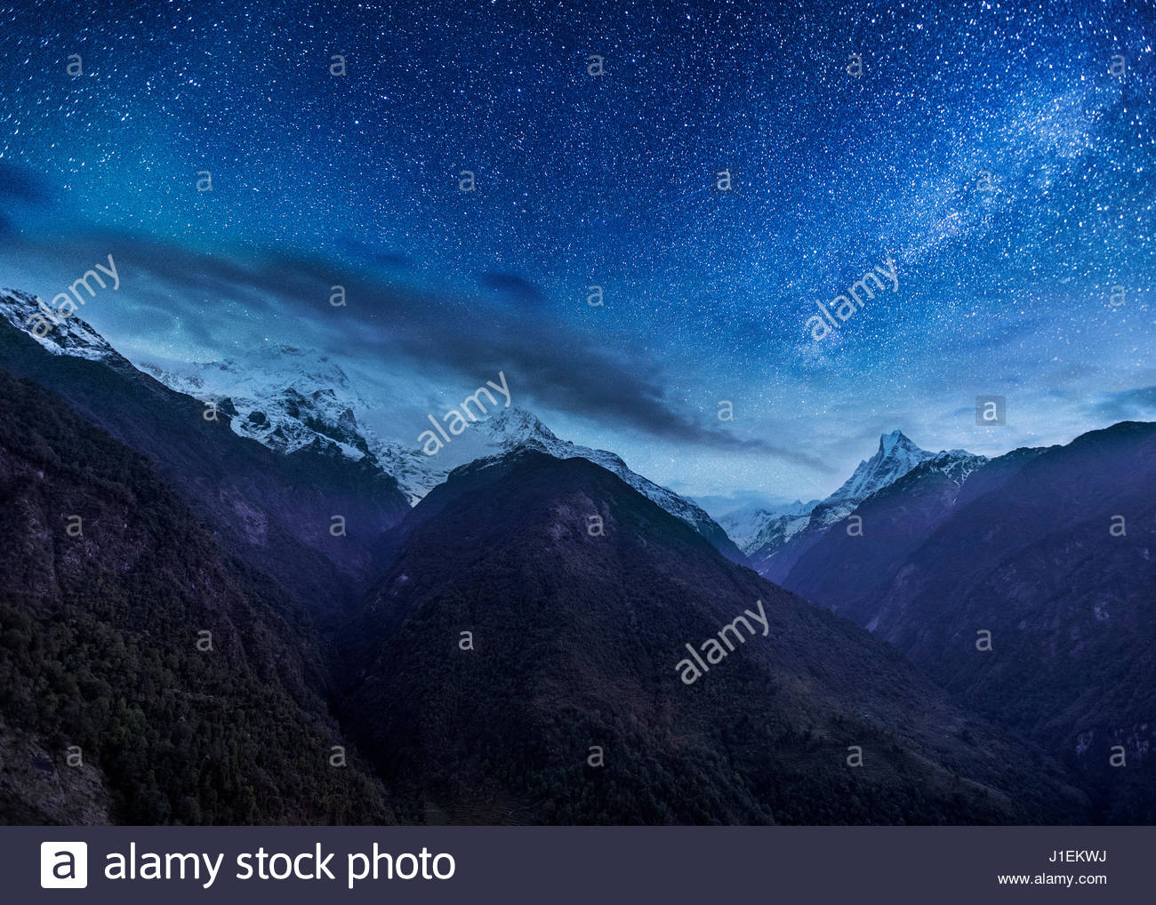 The milky way shines above the hills and valleys of Nepal's Annapurna region. - Stock Image