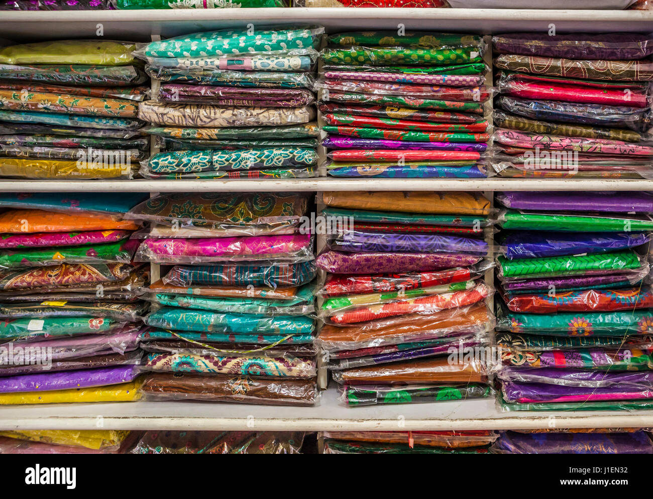 Shelves stocked with colorful clothing at a wedding sari shop in Pune, India. - Stock Image
