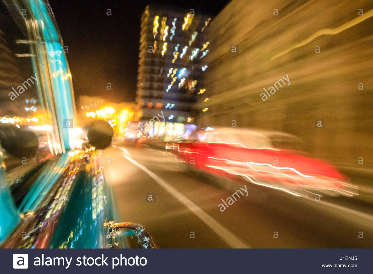 Motion blur of classic American cars cruising at night in Old Havana. - Stock Image