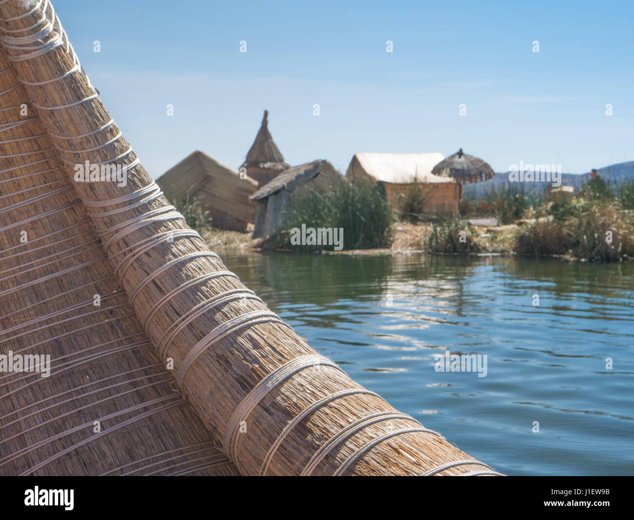 View of the Uros floating reed islands with boats, mysterious Lake Titicaca, Puno Region, Peru - Stock Image