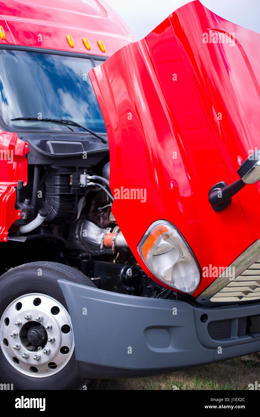 Bright modern red big rig semi-truck parked with open hood to check engine working condition and condition of the - Stock Image