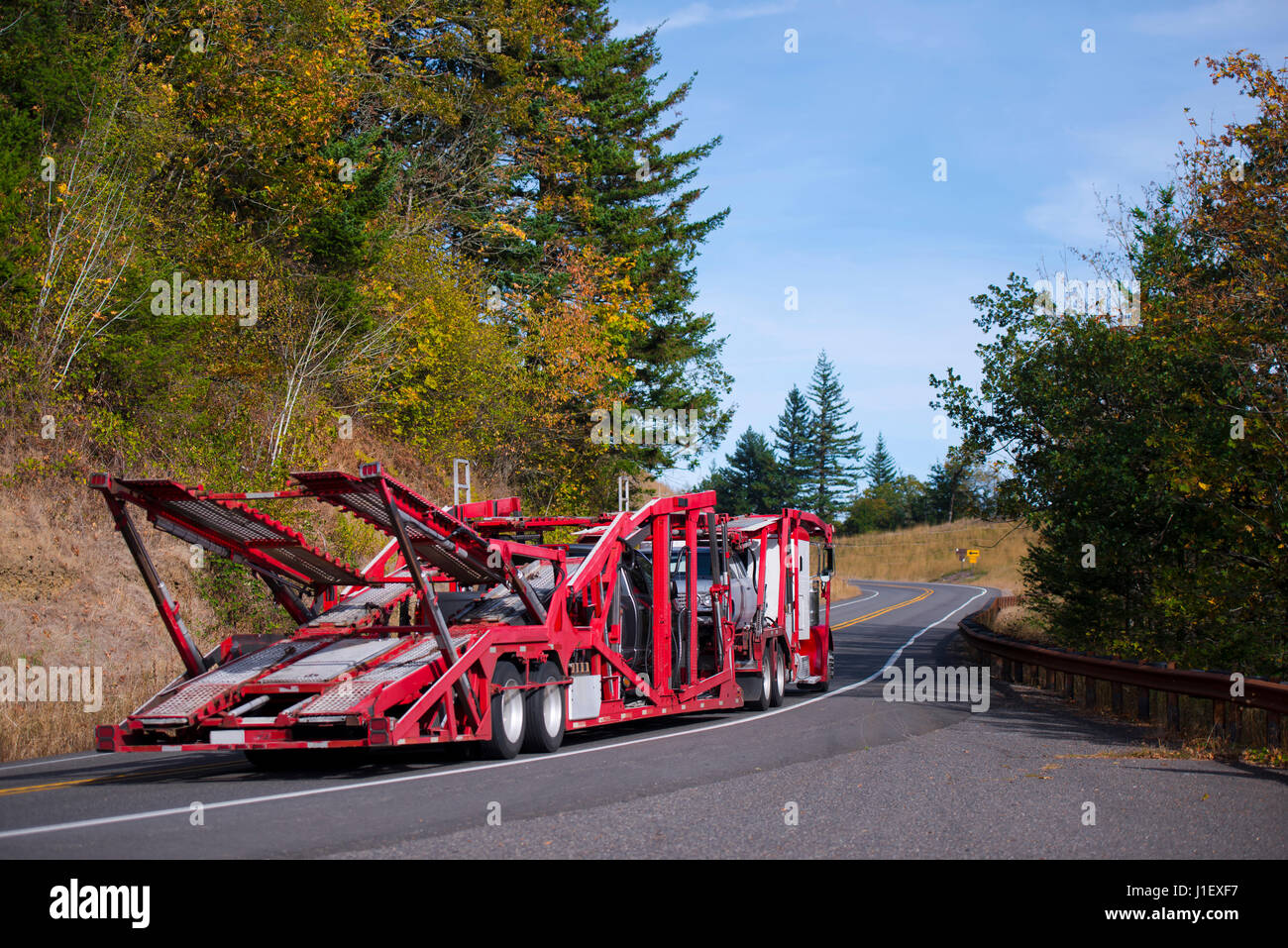 Big rig Semi Truck Car Hauler with red specialized trailer for transportation several cars moving on a winding crooked Stock Photo