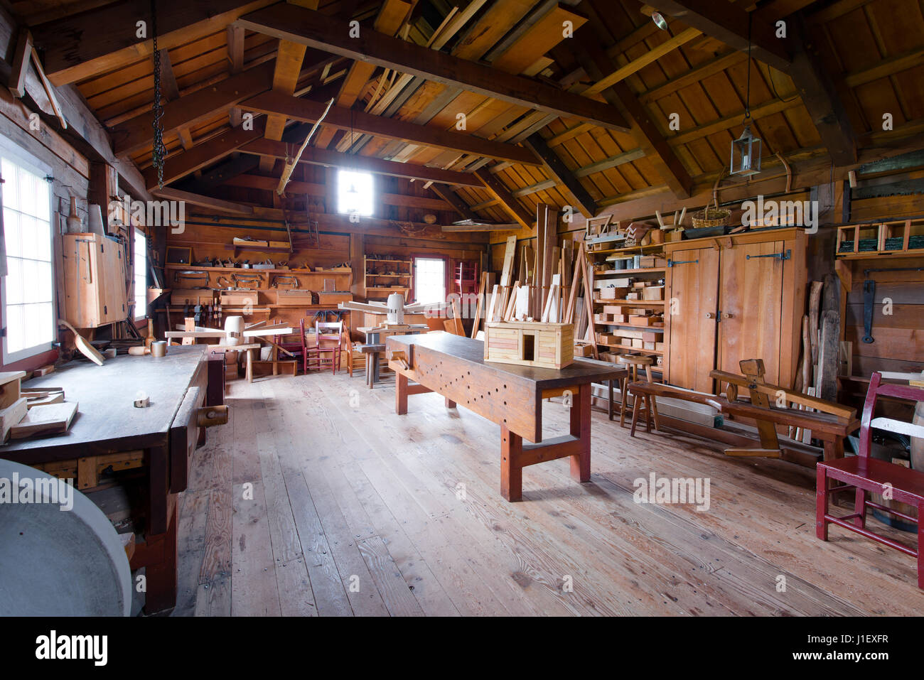 Interior Carpentry Workshop With Workbench, Tools Hanging On The Wooden  Walls, Wooden Blank And Finished Carpentry. Indoor Dried Planks On Beams