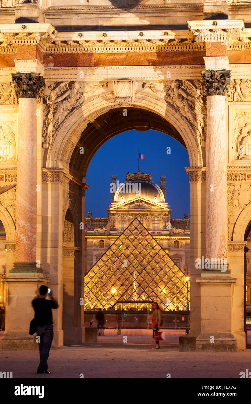 Tourists taking photos at Arc de Triomphe du Carrousel with Musee du Louvre beyond, Paris France - Stock Image