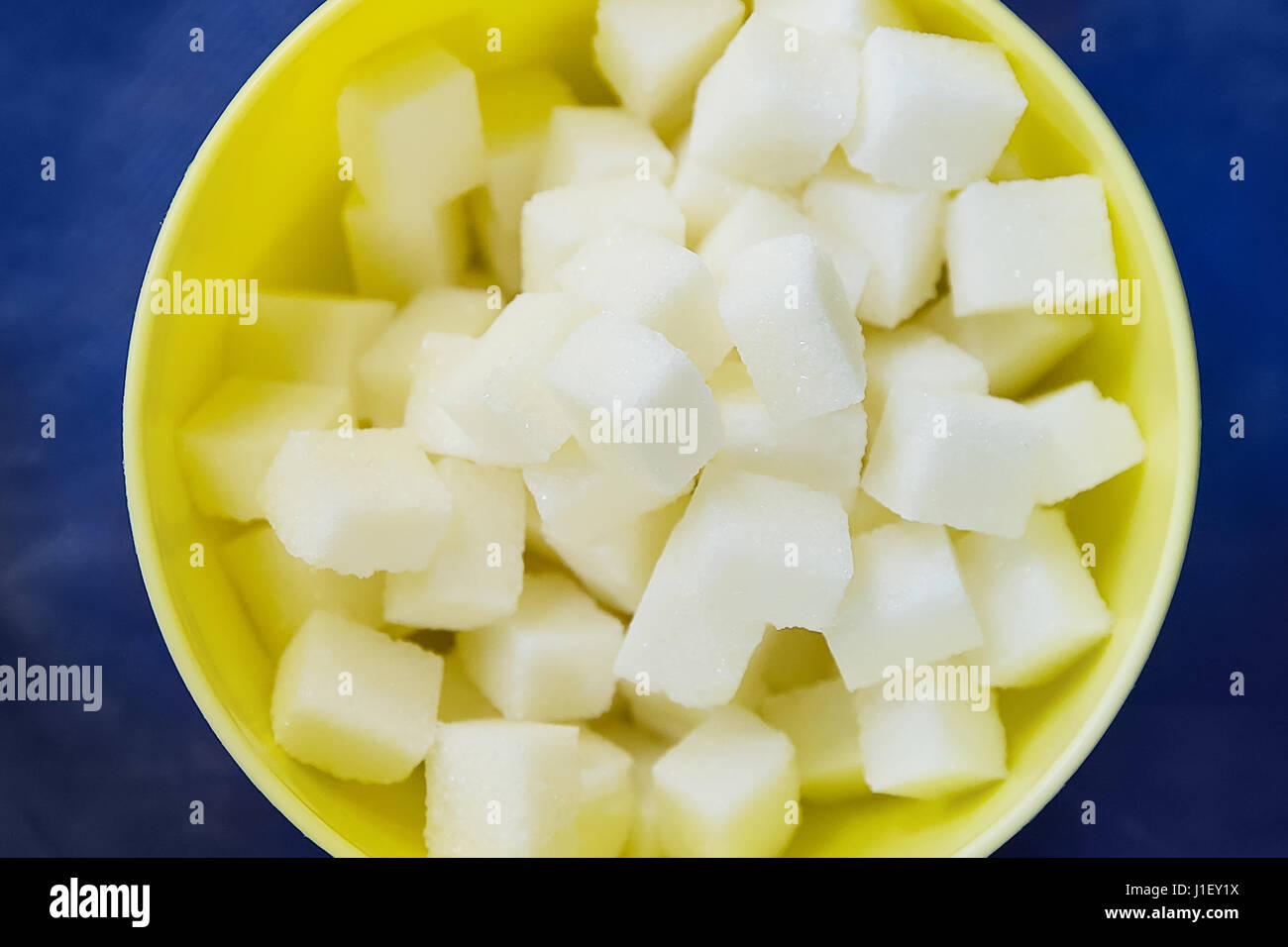 Sugar refined cubes in a yellow plate on a blue table - Stock Image