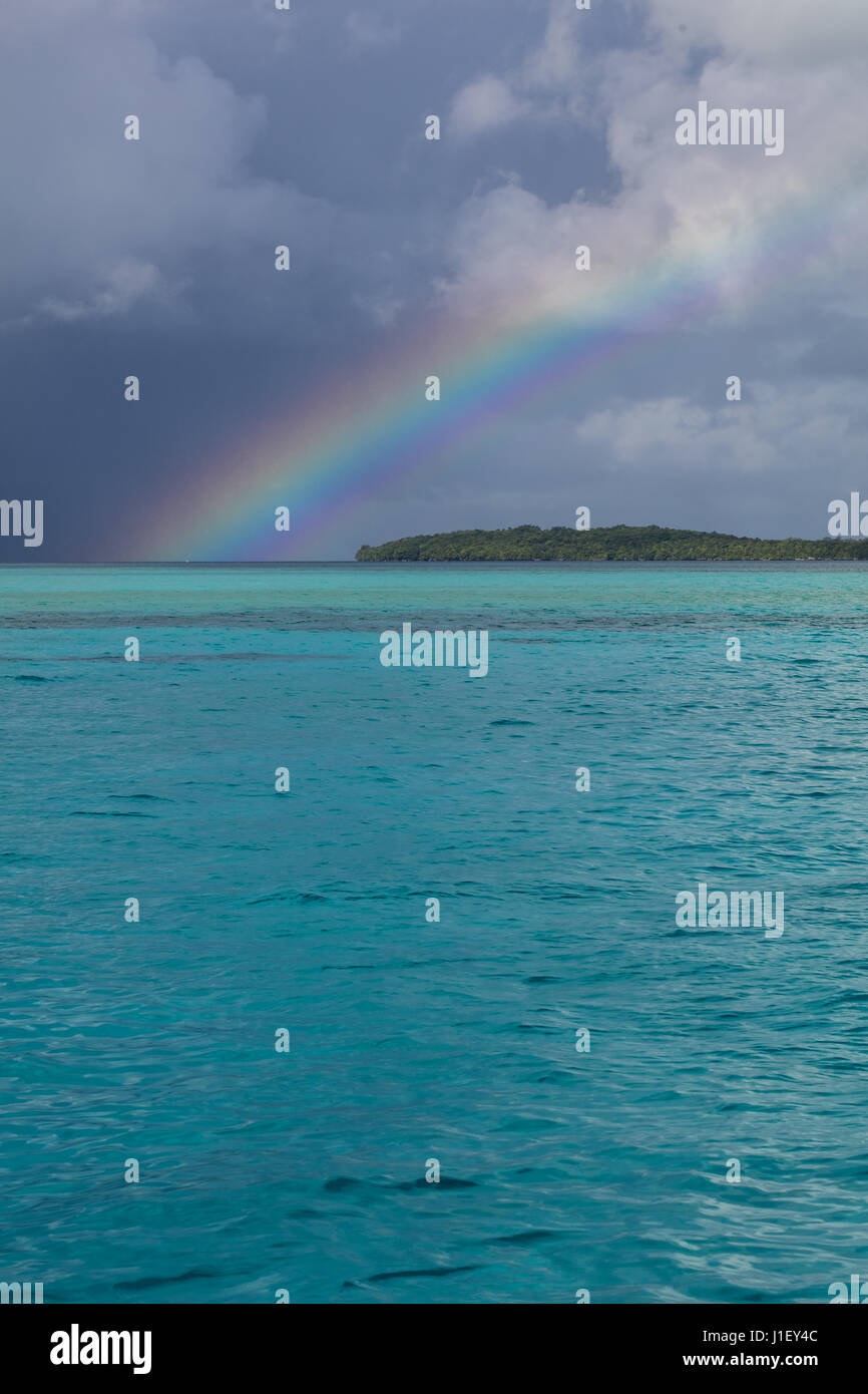 A beautiful rainbow appears over tropical lagoon waters in the Republic of Palau. This Micronesian country is a - Stock Image
