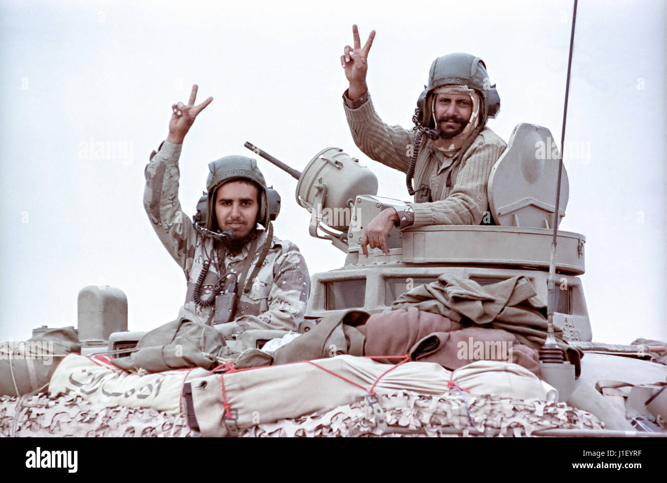 Qatari tank soldiers hold their hands up in the victory sign after leading coalition forces in the recapture of - Stock Image
