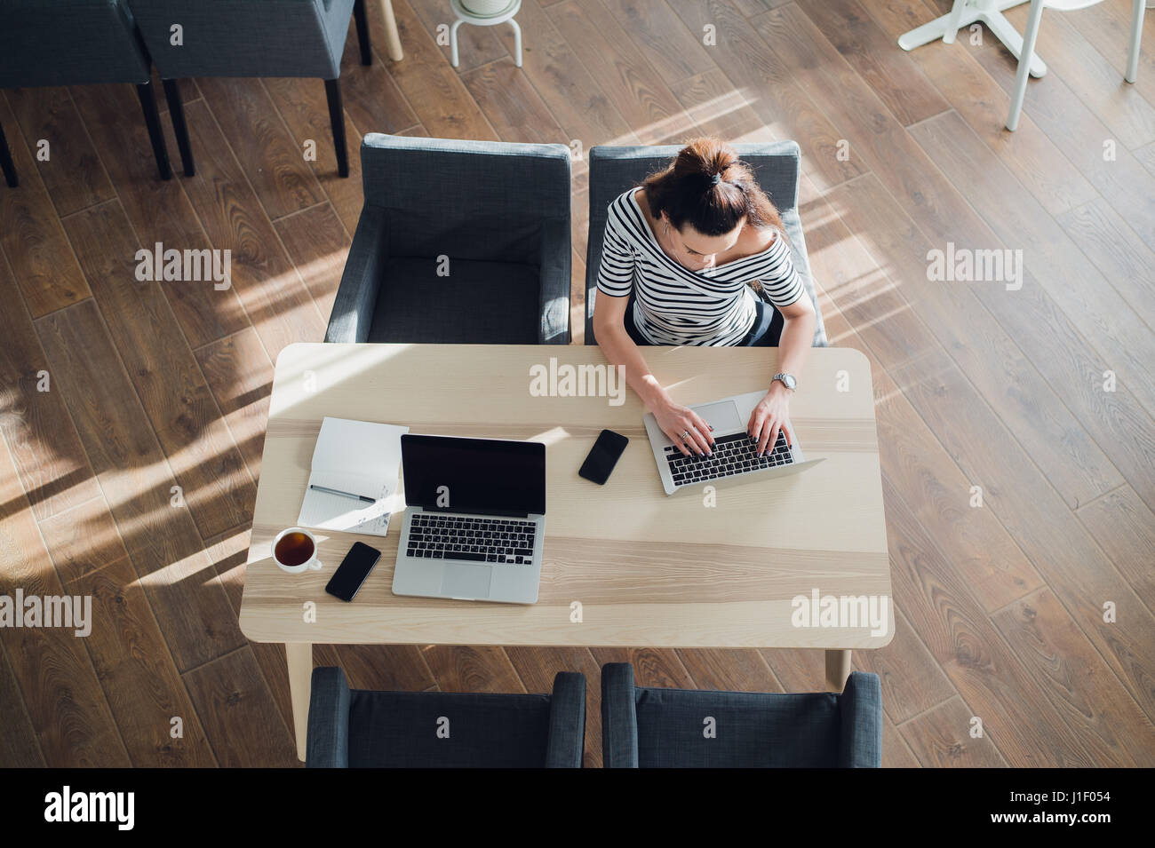 Directly above view of female typing on laptop. Laptop, digital tablet, diary, coffee cup and two smartphones on - Stock Image