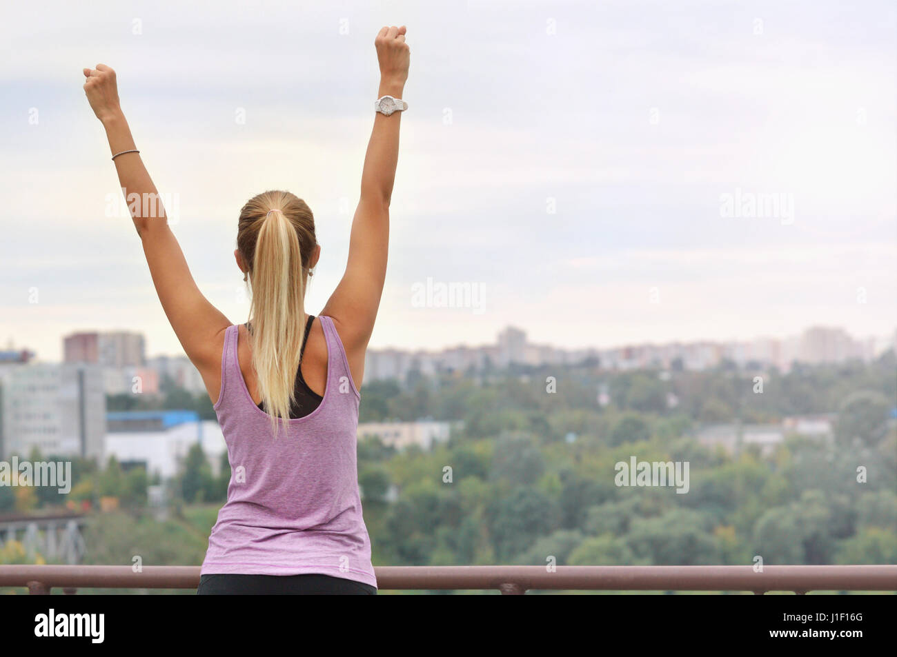 young sporty woman stretching arms preparing for working out stock