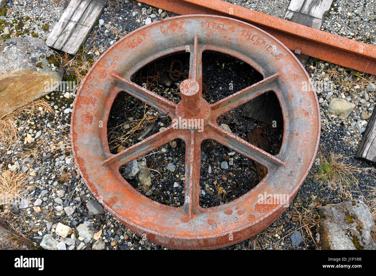 Made in SheffieVild - a steel cable wheel lies as an atrefacts on view at the Denniston Mine historical site near - Stock Image