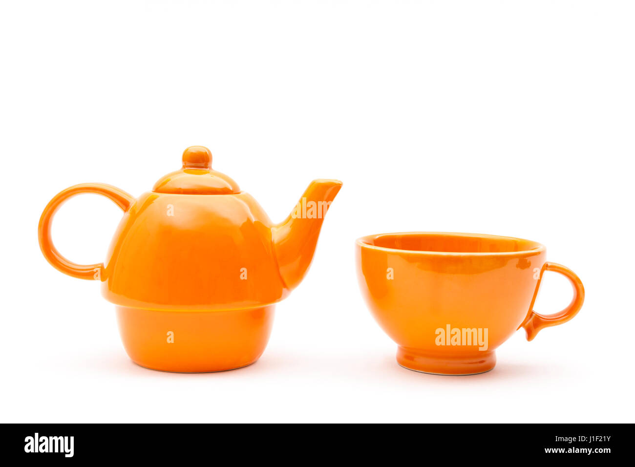 Matching orange teapot and cup isolated on a white background - Stock Image
