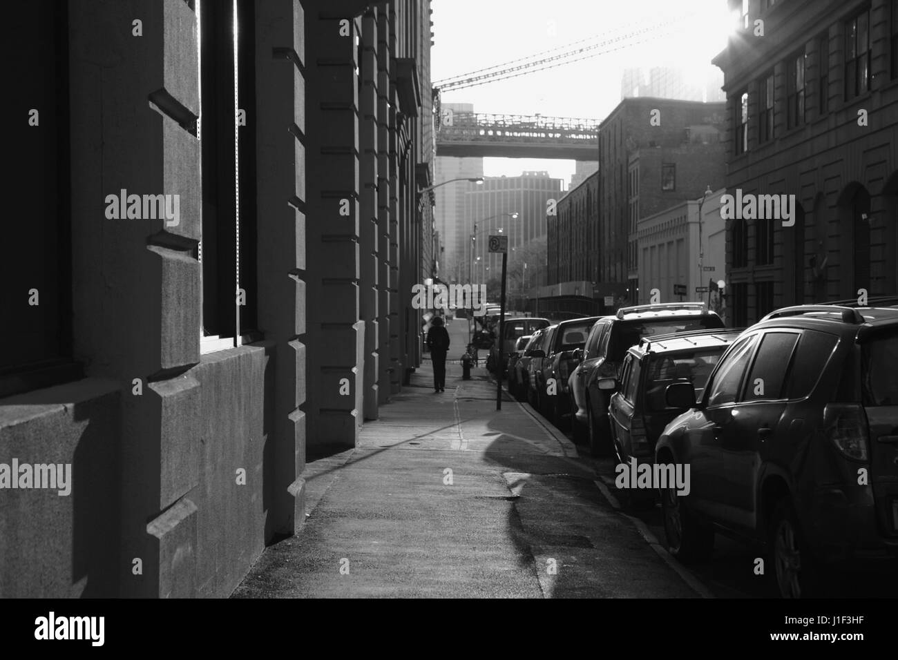Old backstreet in DUMBO Brooklyn, New York at sunset with the Brooklyn Bridge down Water Street. Monochrome, black - Stock Image