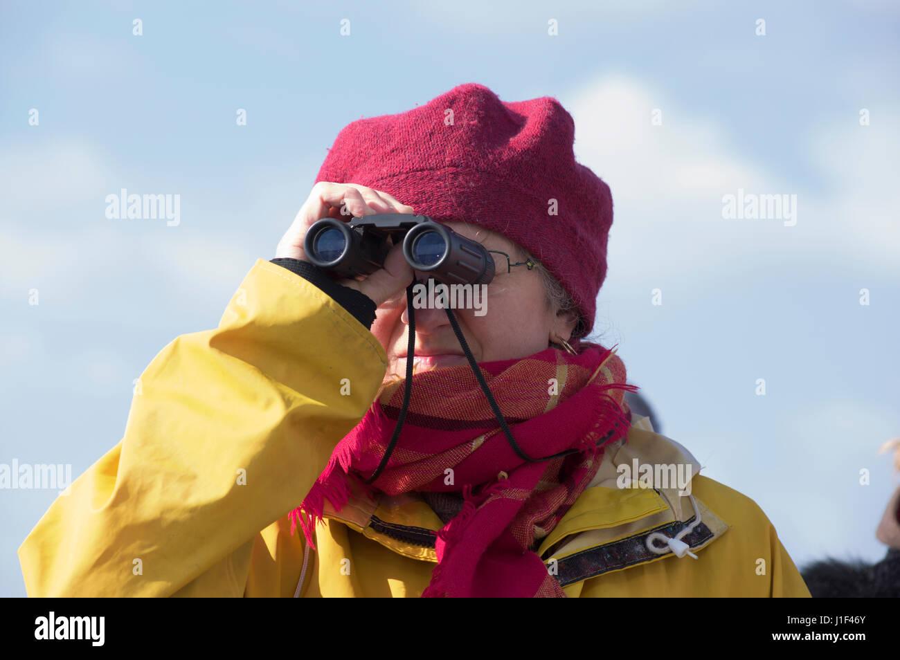 Woman peering through binoculars - Stock Image