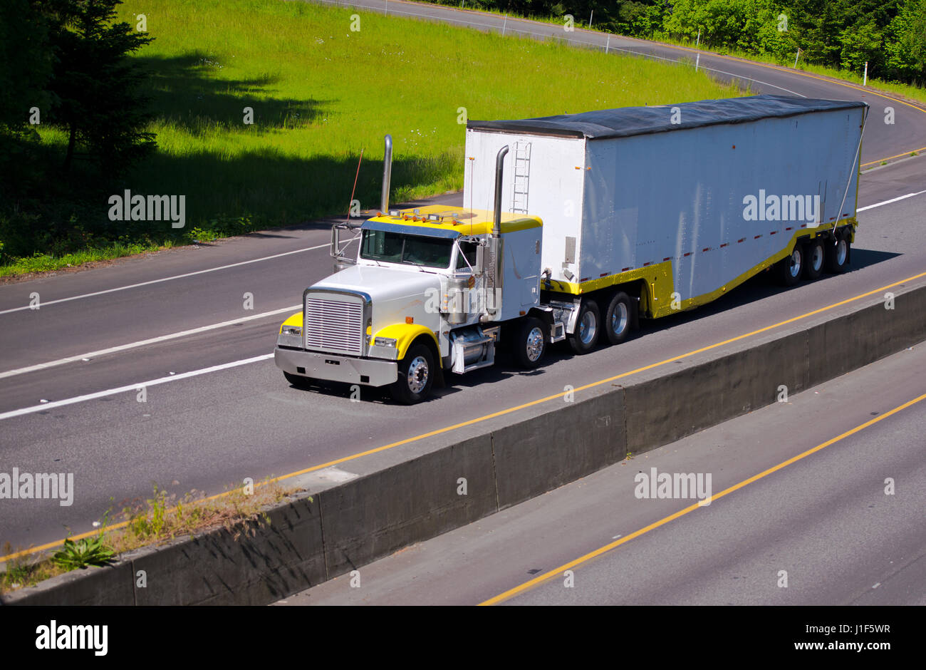 Classic working heavy bonnet truck with high exhaust pipes transporting high bulk trailer on the highway with the - Stock Image
