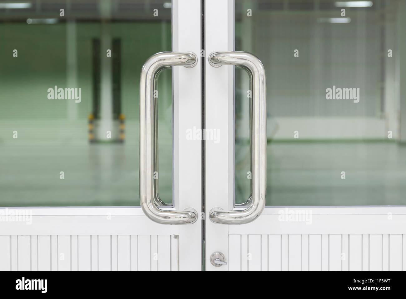 Chrome door handle and glass of aluminium door inside building. - Stock Image