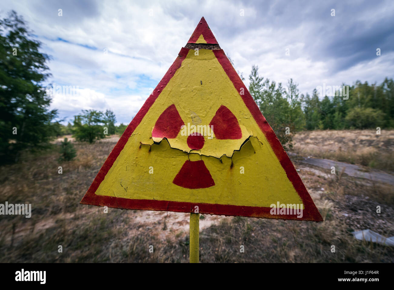 Ionising radiation warning sign on a cemetery in Pripyat ghost city of Chernobyl Nuclear Power Plant Zone of Alienation - Stock Image