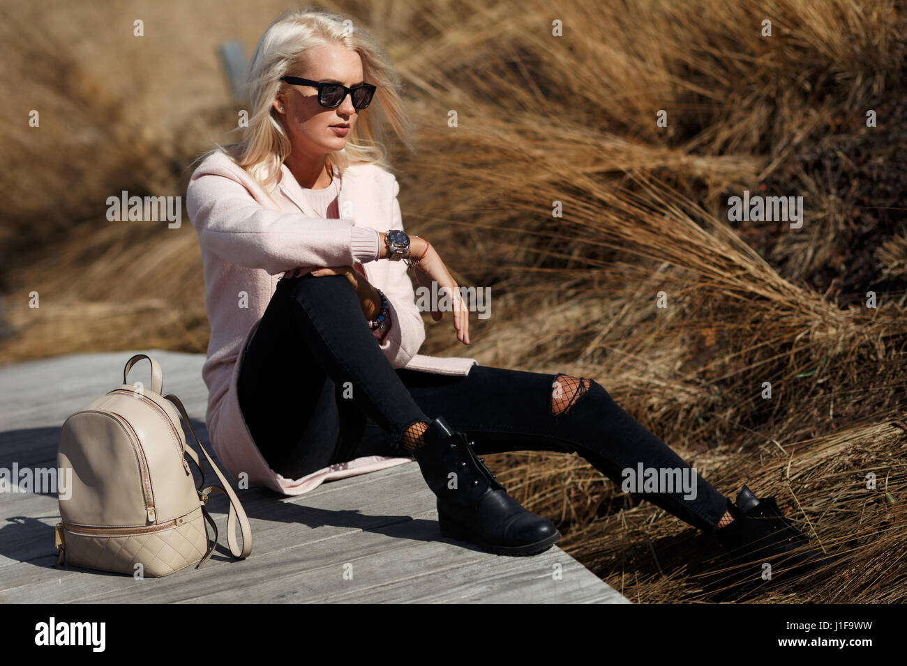 Girl in sunglasses with backpack - Stock Image