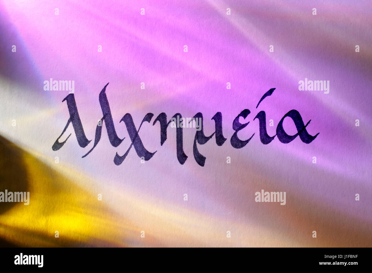 Handwritten word alchemy in greek script under colored lights. Greek language. - Stock Image