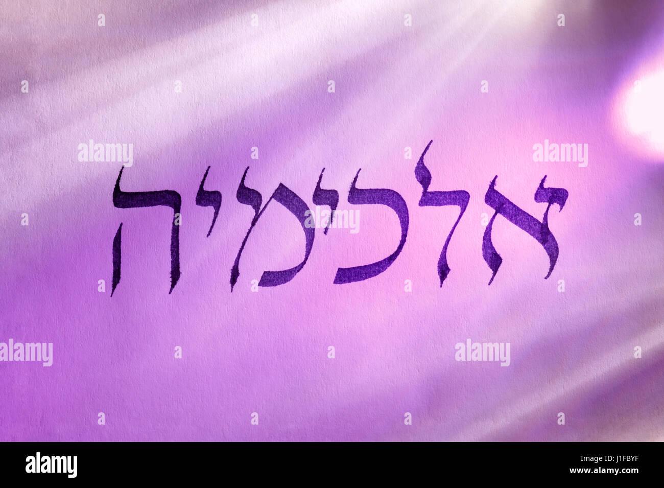 Handwritten word alchemy in hebrew script under colored lights. Hebrew language. - Stock Image