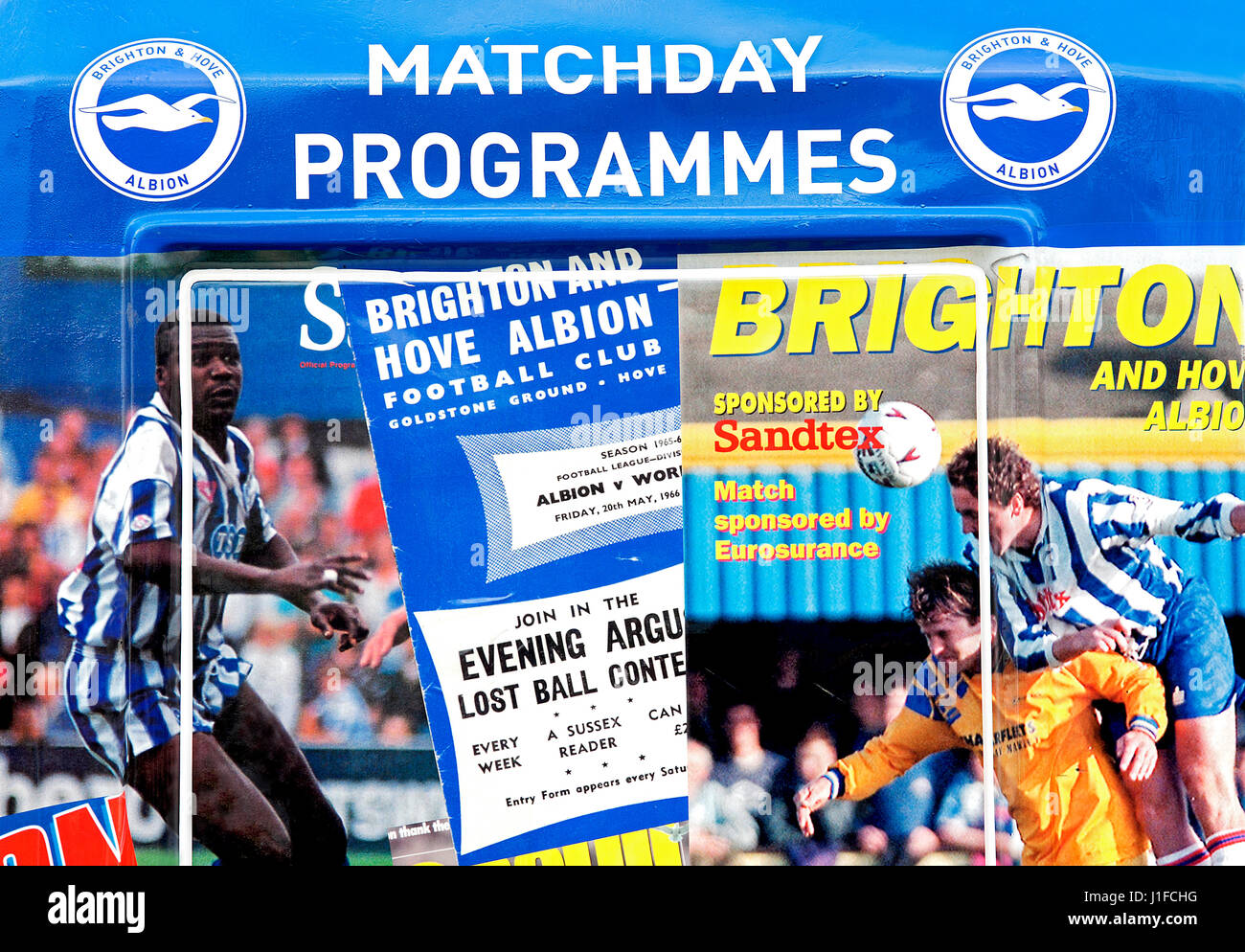 Magazine covers and famous football players of Brighton and Hove Albion plastered on the matchday programmes booth - Stock Image