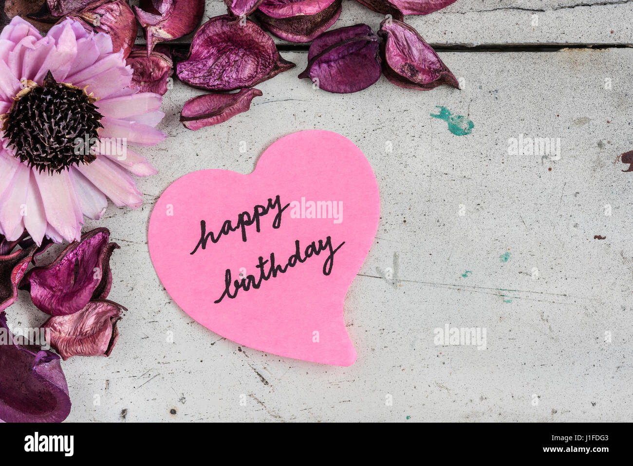 Happy birthday note in heart shape paper with pink flowers and happy birthday note in heart shape paper with pink flowers and purple petal on grungy white wooden table izmirmasajfo
