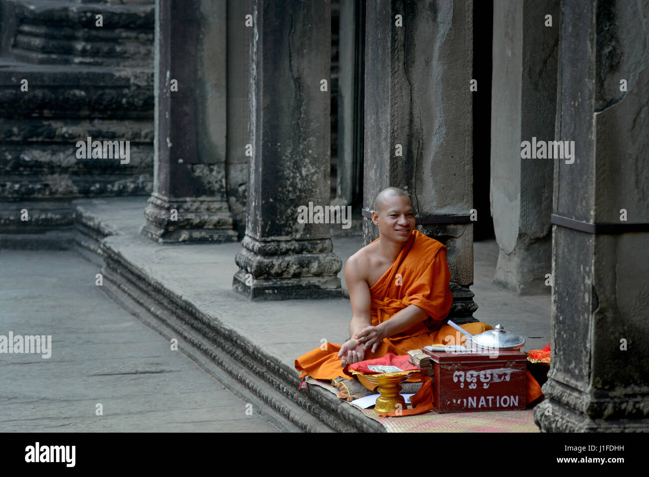 Buddhist monk sells prayers in the Angkor Wat temple complex in Siem Reap, Cambodia. - Stock Image
