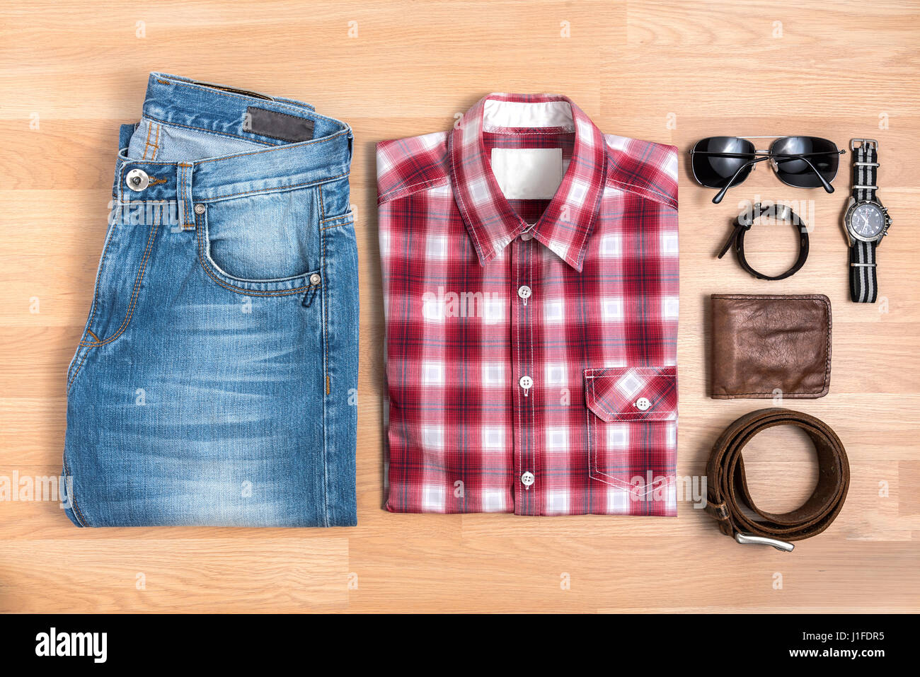 Men's casual outfits with accessories on wooden table, Red plaid shirt and blue jeans with eyeglasses, bracelet, Stock Photo