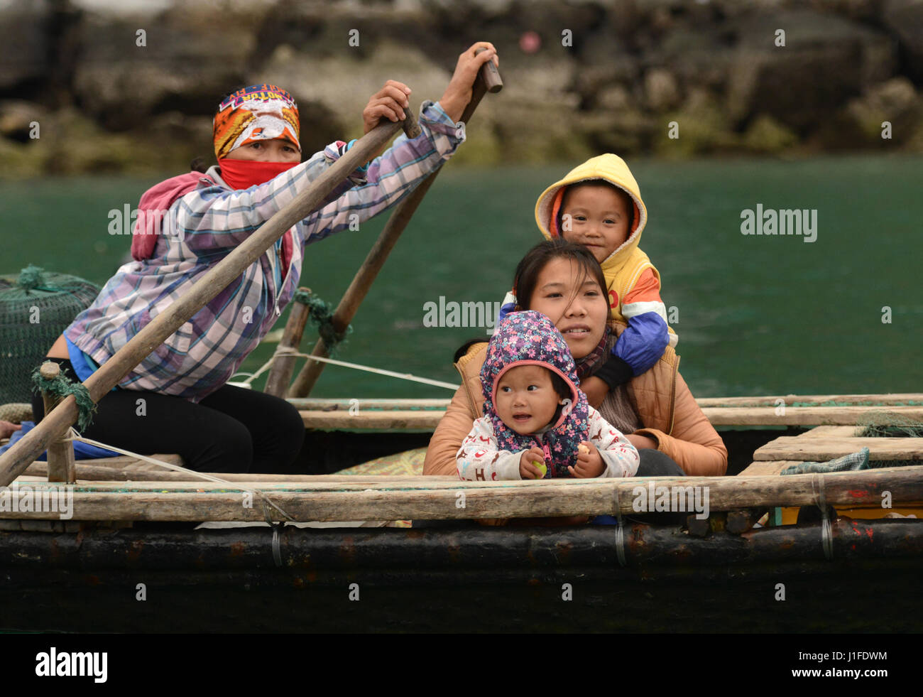 Fisherman's families in Halong Bay contribute to the family income by selling snacks and souvenirs to the passing - Stock Image