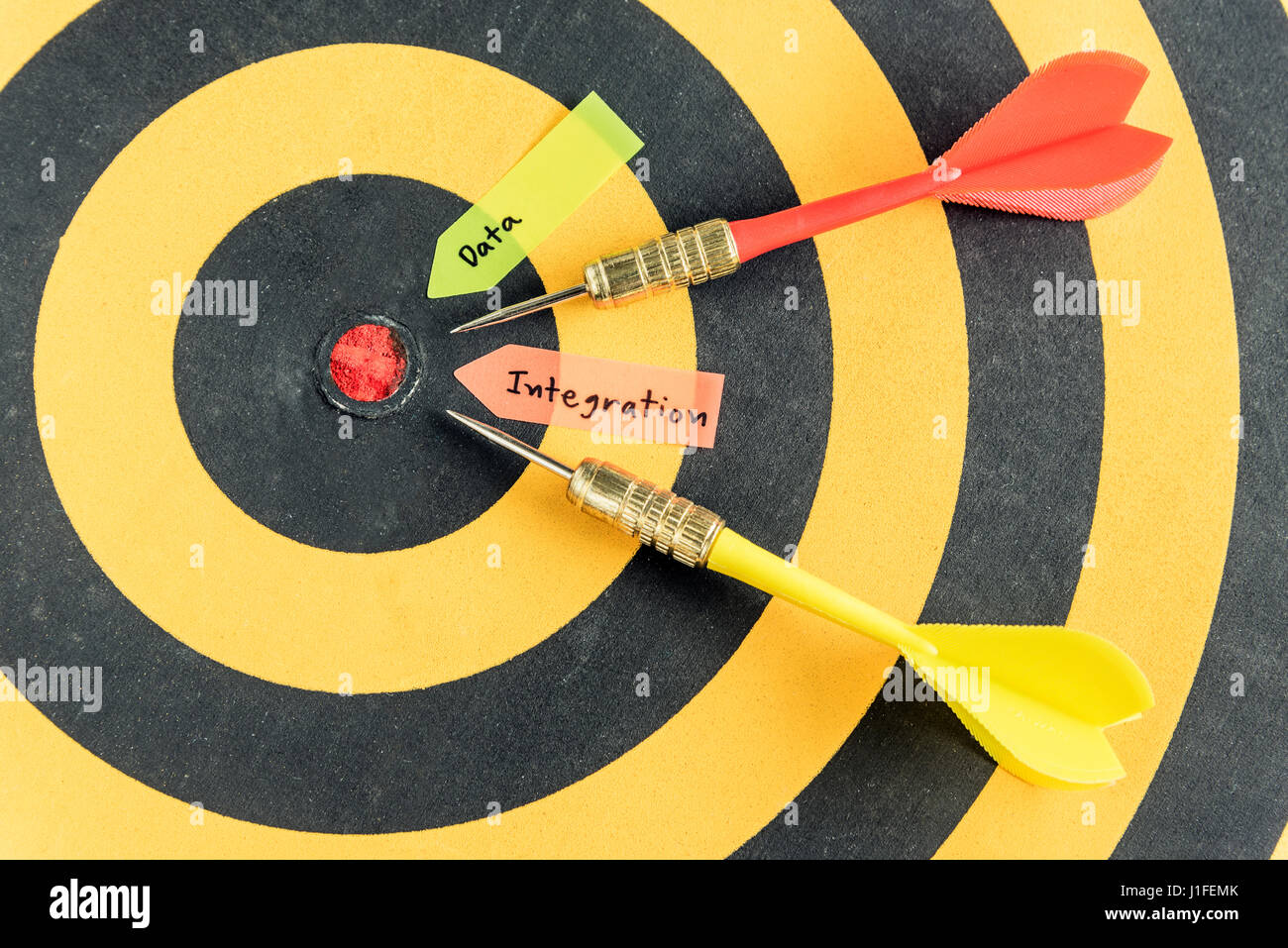 Words data integration with dart target run in to bullseye over dartboard background, Data integration concept - Stock Image