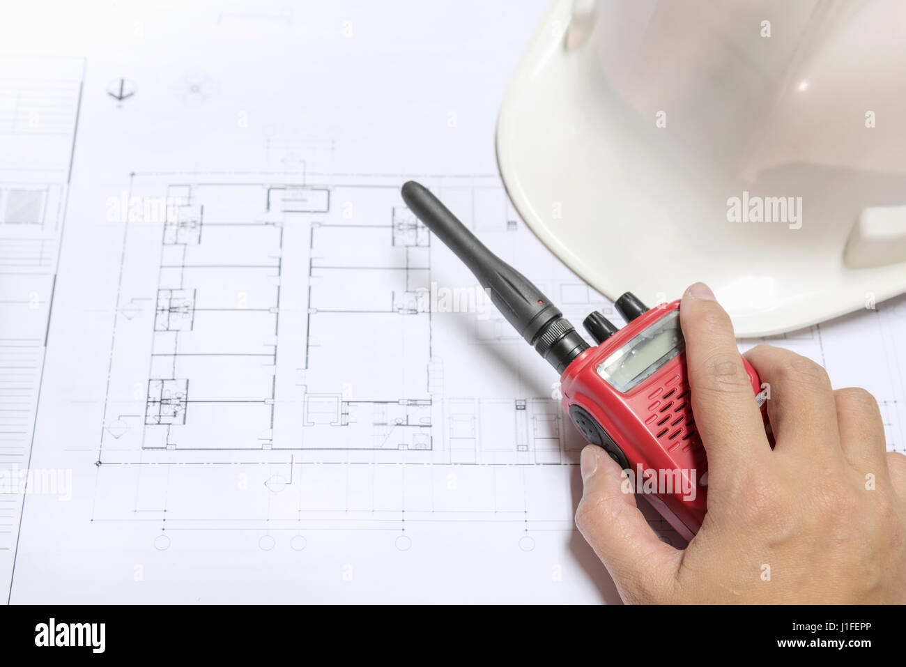 Engineer hand holding radio communication on architectural engineer hand holding radio communication on architectural blueprints paper near helmet architect engineering and contractor concept malvernweather Gallery